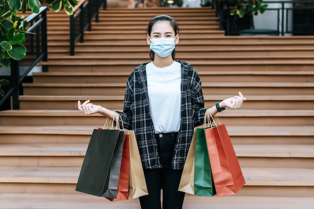 Portret młodej kobiety w masce ochronnej niosącej wiele papierowych toreb na zakupy