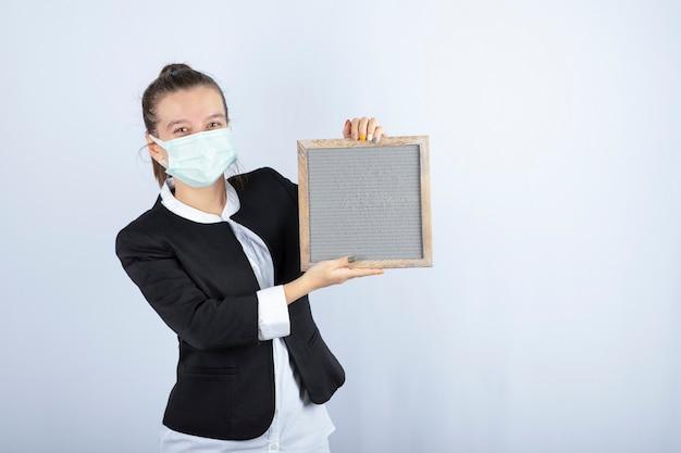 Portret młodej kobiety w masce trzymając ramkę na białej ścianie. wysokiej jakości zdjęcie