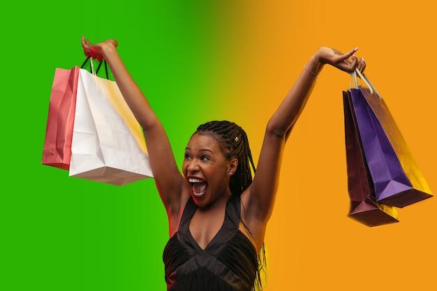 Portret młodej kobiety w neonowym świetle z torbami na zakupy, czarny piątek