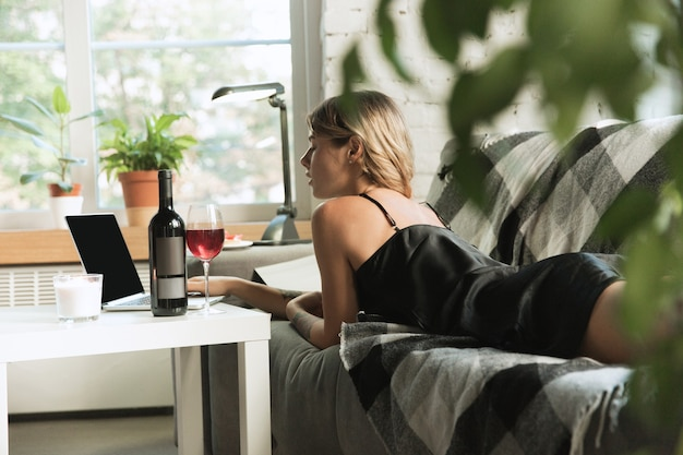 Portret młodej kobiety w nowoczesnym mieszkaniu na kanapie