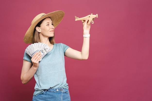 Portret młodej kobiety w okularach przeciwsłonecznych, kapeluszu z pieniędzmi i drewnianym samolocie na różowej ścianie