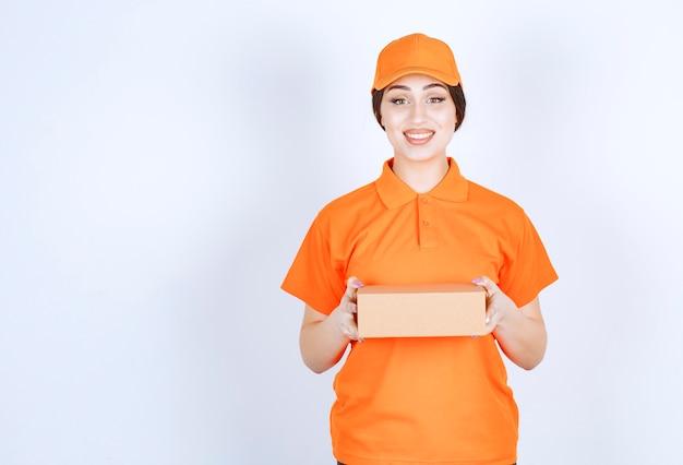 Portret młodej kobiety w pomarańczowym unishape trzymającym pudełko