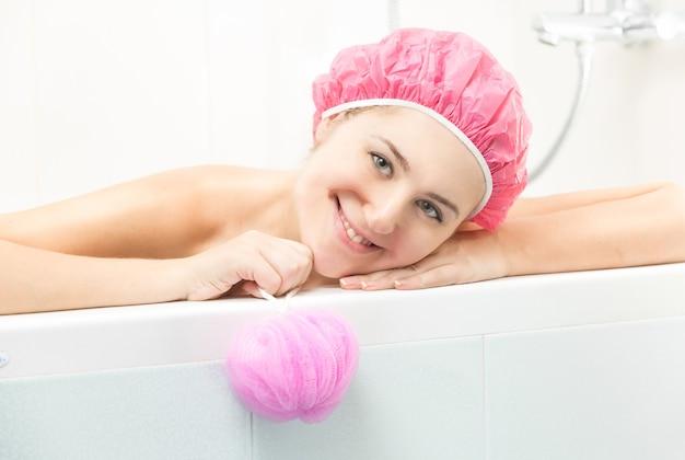 Portret młodej kobiety w różowej czepku pozuje w wannie