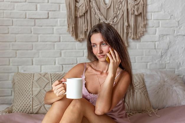 Portret młodej kobiety w różowej piżamie za pomocą smartfona, siedząc na łóżku w domu. czatować z przyjaciółmi. zakupy online koncepcja. relaksująca filiżanka gorącej kawy lub herbaty.