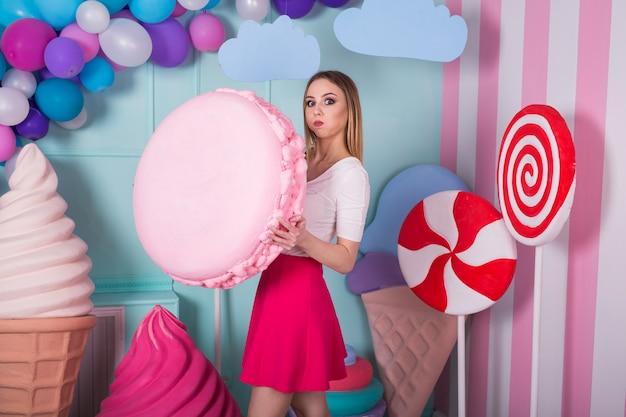 Portret młodej kobiety w różowej sukience gospodarstwa duże makaronik i pozowanie. niesamowita dziewczyna o słodkich zębach otoczona zabawkowymi słodyczami.