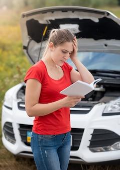 Portret młodej kobiety w rozpaczy, czytającej instrukcję obsługi zepsutego samochodu w polu
