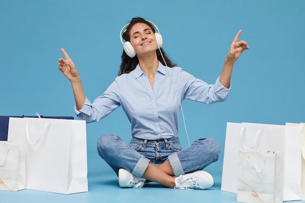Portret młodej kobiety w słuchawkach siedzi na podłodze wśród toreb na zakupy i słuchanie muzyki na niebieskim tle