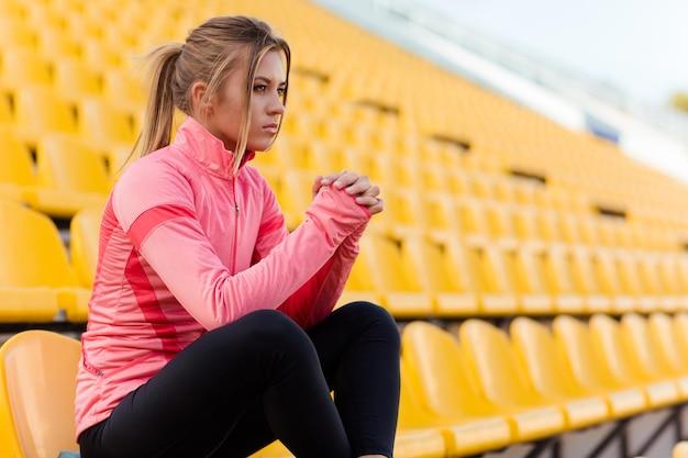Portret młodej kobiety w sportowej odzieży siedzącej na krześle na stadionie