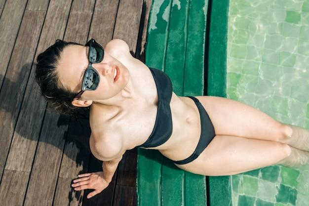 Portret młodej kobiety w stroju kąpielowym, siedząc na basenie