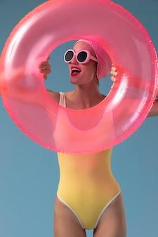 Portret młodej kobiety w stroju kąpielowym z pierścieniem do pływania