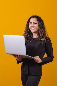 Portret młodej kobiety w stroju wykonawczym z laptopem na żółtym tle. kobieta pracuje z laptopem. pionowy