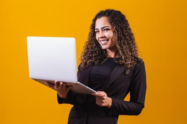 Portret młodej kobiety w stroju wykonawczym z laptopem na żółtym tle. kobieta pracuje z laptopem