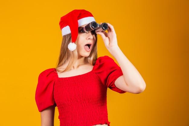 Portret młodej kobiety w świątecznych ubraniach patrzącej przez lornetkę