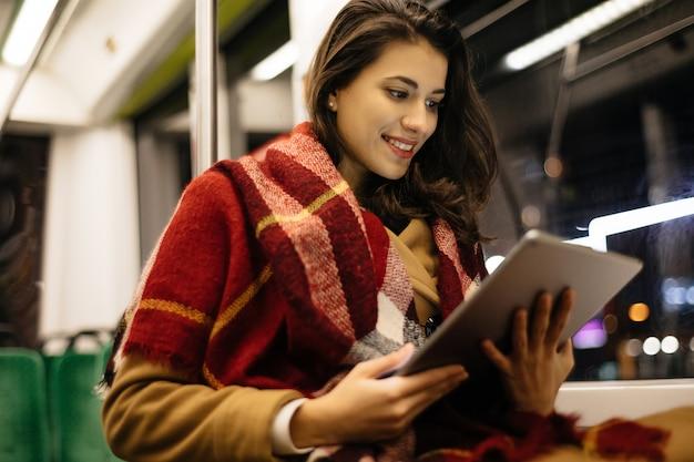 Portret młodej kobiety w transporcie publicznym, siedzi i korzysta z komputera typu tablet w nowoczesnym tramwaju.