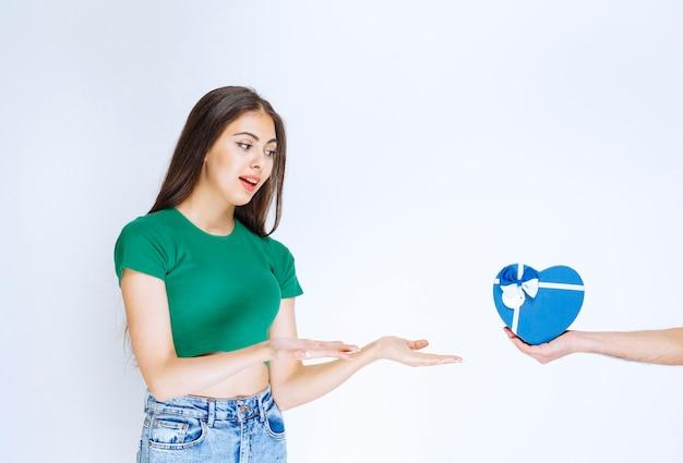 Portret młodej kobiety w zielonej koszuli otrzymującej niebieskie pudełko od kogoś.