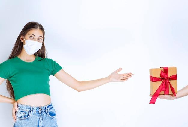 Portret młodej kobiety w zielonej koszuli stojącej, podczas gdy ktoś daje jej prezent.