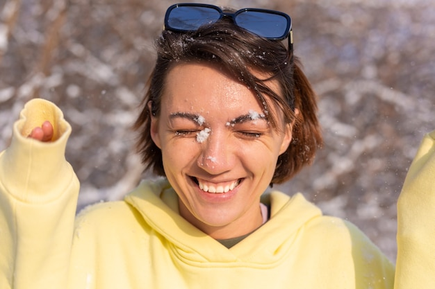Portret młodej kobiety w zimowym lesie w słoneczny dzień ze śnieżnobiałym uśmiechem, wygłupiać się