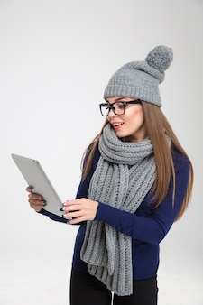 Portret młodej kobiety w zimowym suknie przy użyciu komputera typu tablet na białej ścianie