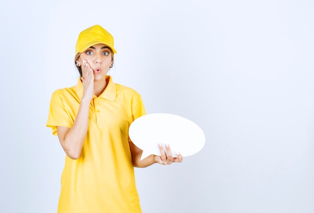 Portret młodej kobiety w żółtym mundurze trzyma pusty pusty dymek.