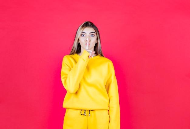 Portret młodej kobiety w żółtym stroju dającej znak ciszy