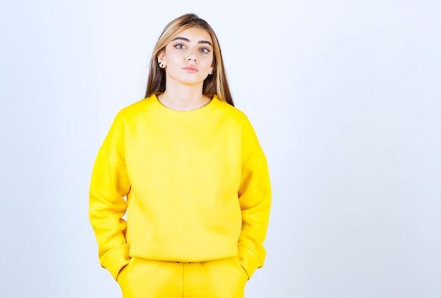 Portret młodej kobiety w żółtym stroju pozuje i stoi