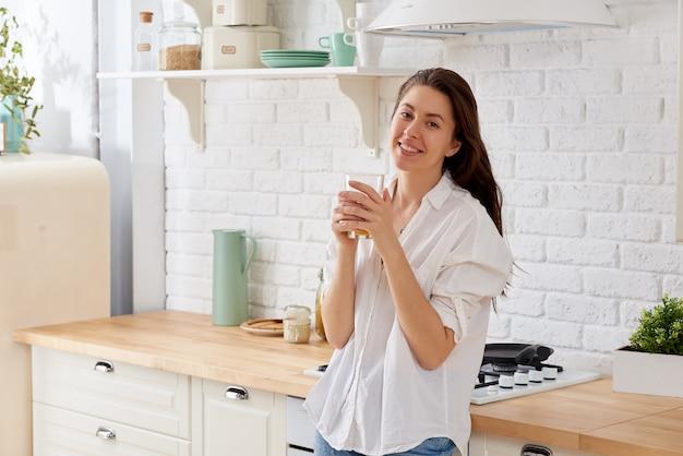 Portret młodej kobiety woda pitna w kuchni w domu