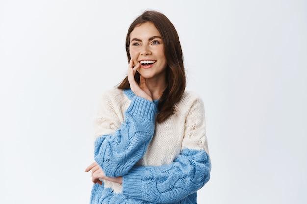 Portret młodej kobiety wpatrującej się w lewo w przestrzeń kopii i uśmiechniętej rozbawionej, obserwującej coś interesującego na bok, stojącej w swetrze na tle białej ściany