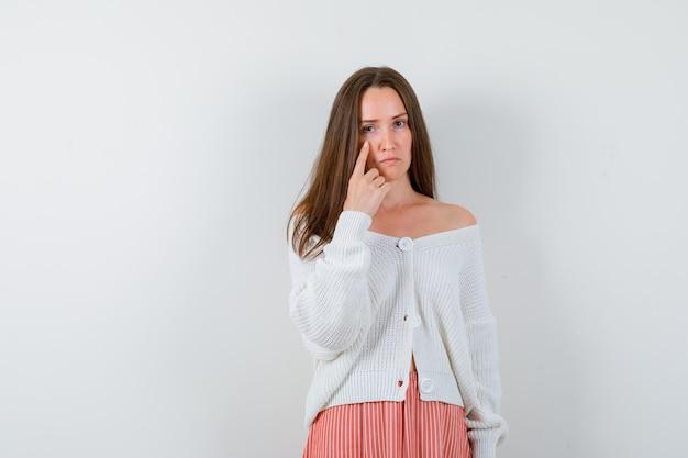 Portret młodej kobiety, wskazując na jej powiekę w sweter na białym tle