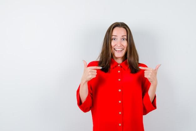 Portret młodej kobiety, wskazując na siebie w czerwonej bluzce i patrzący szczęśliwy widok z przodu