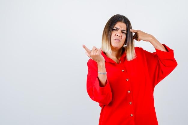 Portret młodej kobiety wskazującej na głowę i na bok w czerwonej zbyt dużej koszuli i patrzącej niezdecydowany widok z przodu