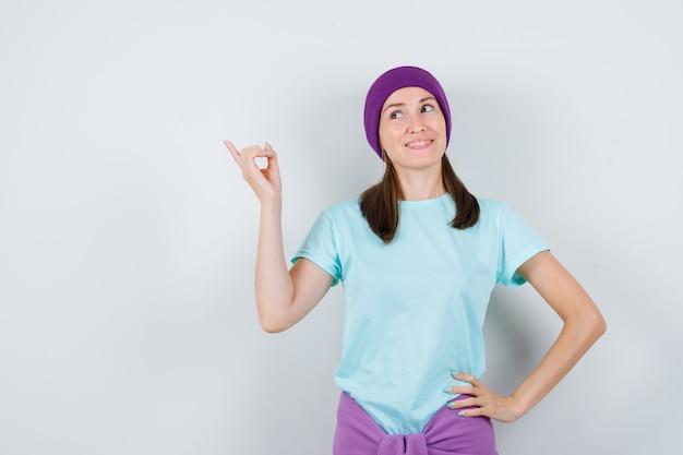 Portret młodej kobiety wskazującej na lewy górny róg w t-shirt, czapka i patrząca marzycielski widok z przodu