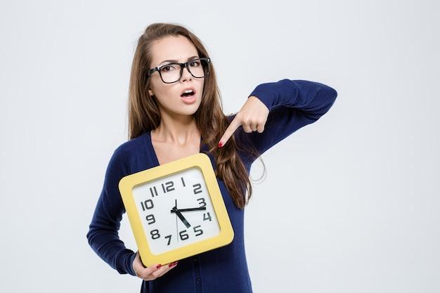 Portret młodej kobiety wskazujący palec na zegar ścienny izolować na białym tle