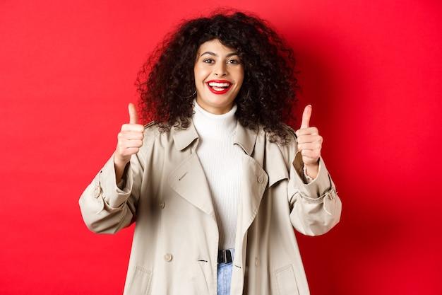 Portret młodej kobiety wyglądającej szczęśliwie, ubrana w trencz i pokazująca kciuki do góry, powiedz tak, zaakceptuj i chwal coś dobrego, czerwona ściana.