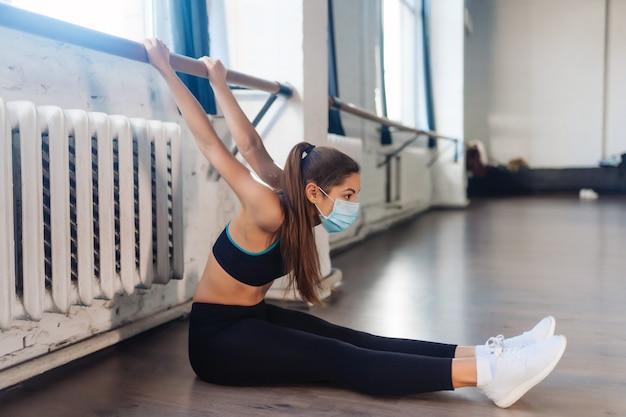 Portret młodej kobiety wykonującej ćwiczenia na siłowni.
