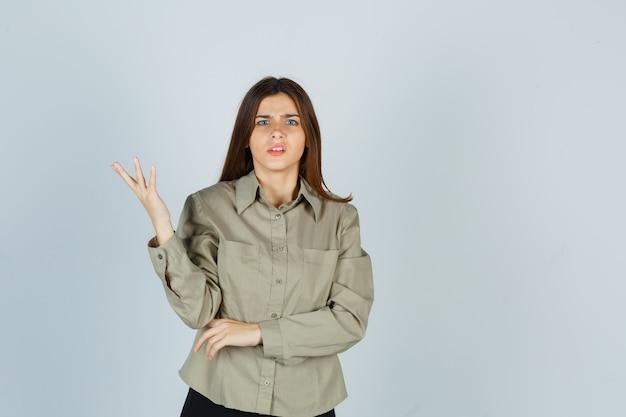 Portret młodej kobiety wykonującej gest zadawania pytań w koszuli, spódnicy i patrząc zdziwiony widok z przodu