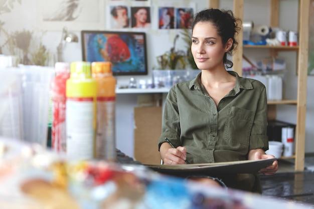Portret młodej kobiety wykonującej twórcze zajęcie siedzącej w nowoczesnym warsztacie i pracującej, cieszącej się procesem tworzenia czegoś pięknego, patrzącej z ukosa z zadowolonym, natchnionym wyrazem twarzy