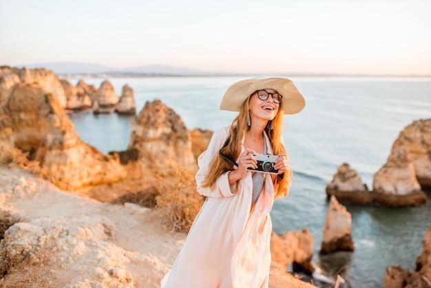 Portret młodej kobiety z aparatem fotograficznym, cieszącej się wspaniałym widokiem na skaliste wybrzeże podczas wschodu słońca w lagos na południu portugalii