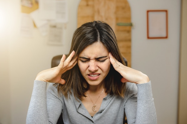Portret młodej kobiety z bólem głowy, siedząc na krześle podczas pracy w biurze