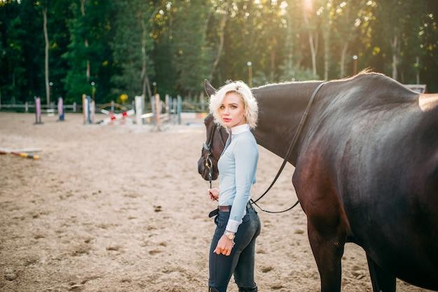 Portret młodej kobiety z brązowym koniem.