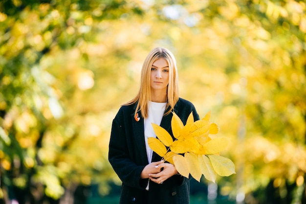 Portret młodej kobiety z bukietem żółtych liści