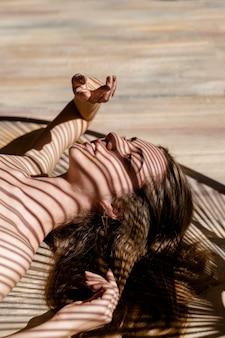 Portret młodej kobiety z cieniami liści palmowych na twarzy. koncepcja opalania, wakacji, czasu letniego.