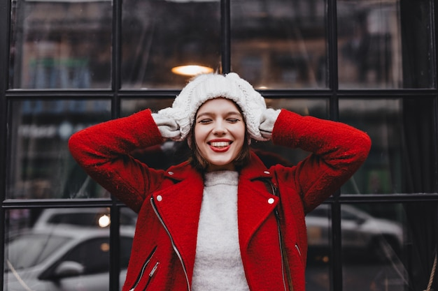 Portret młodej kobiety z czerwoną szminką i śnieżnobiałym uśmiechem, ubrana w białą czapkę, rękawiczki i wełnianą kurtkę przed oknem w czarnej ramce.