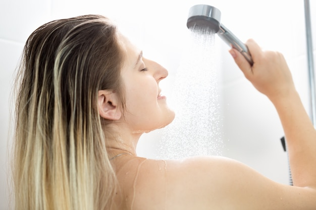 Portret młodej kobiety z długimi blond włosami myjącymi pod prysznicem