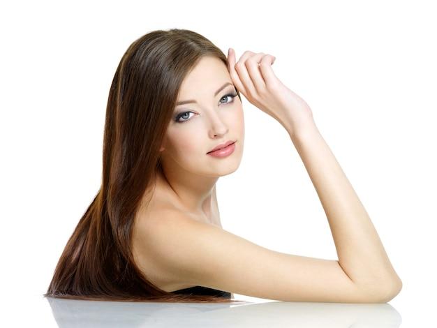 Portret młodej kobiety z długimi prostymi, pięknymi włosami na białym tle