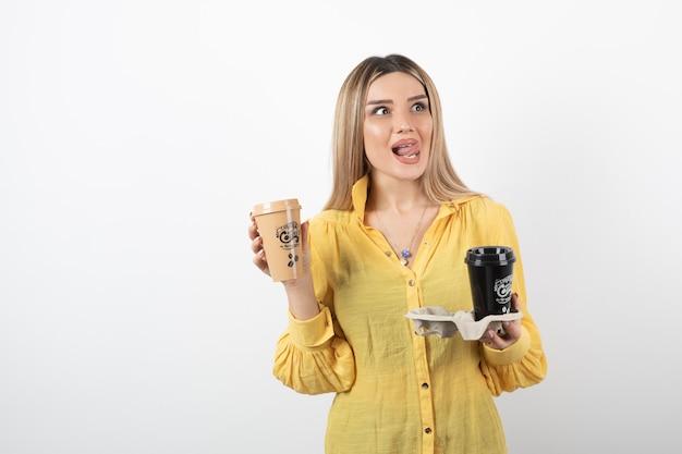 Portret młodej kobiety z filiżankami kawy na białej ścianie.