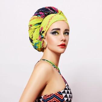 Portret młodej kobiety z jasnym makijażem i modny szalik głowy na jasnym tle