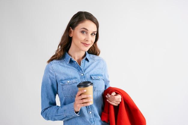 Portret młodej kobiety z jednorazową filiżanką kawy