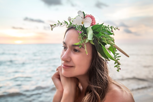 Portret młodej kobiety z kompozycją kwiatów na głowie na tle oceanu o zachodzie słońca.