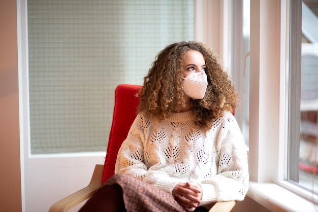 Portret młodej kobiety z kręconymi włosami i smutnymi oczami w kolorze białym medyczna maska ochronna siedzi przy oknie