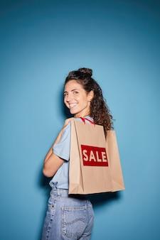 Portret młodej kobiety z kręconymi włosami robi zakupy na sprzedaż ona uśmiecha się stojąc na niebieskim tle